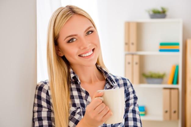 Ritratto di giovane donna graziosa che ha pausa e che tiene tazza con tè