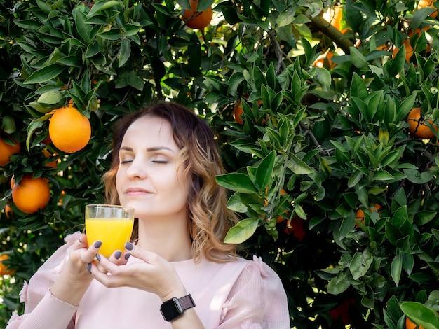Ritratto di giovane donna graziosa che tiene un bicchiere di succo d'arancia vicino all'albero di arancio