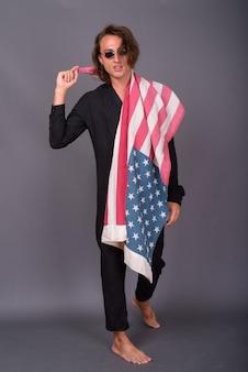 Ritratto di giovane uomo americano orgoglioso che tiene la bandiera degli stati uniti