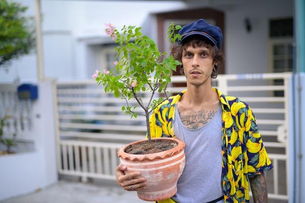 Ritratto di giovane uomo ribelle che tiene vaso di fiori all'aperto