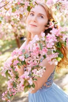 Ritratto di una giovane donna dai capelli rossi di fioritura primaverile sakura nel parco il concetto di profumo fragrante e giovanile