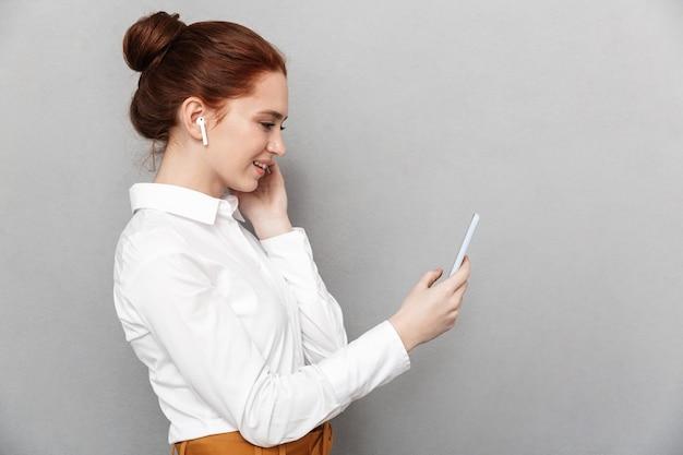 Ritratto di giovane imprenditrice rossa 20s che indossa auricolari tenendo e guardando lo smartphone in ufficio isolato su gray