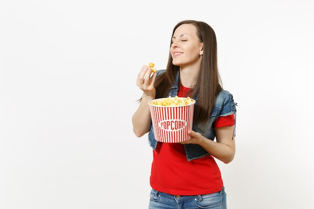 Ritratto di giovane bella donna rilassante con gli occhi chiusi in abiti casual guardando film, tenendo secchio di popcorn, mangiando, godendo isolato su sfondo bianco. emozioni nel concetto di cinema.