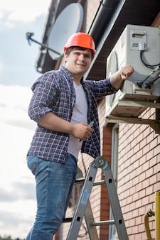 Ritratto di giovane riparatore che installa il condizionatore d'aria sulla parete esterna