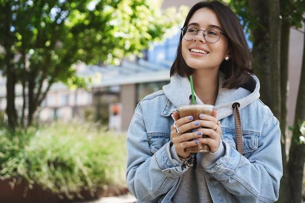 Ritratto di giovane ragazza romantica e sognante in occhiali e giacca di jeans, alzando lo sguardo contemplando gli uccelli che cantano in una luminosa giornata perfetta, tenendo in mano il latte di ghiaccio, bevendo caffè e sedendosi su una panchina del parco sorridendo.
