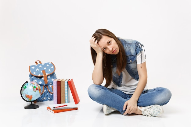 Ritratto di giovane studentessa triste esausta in abiti di jeans che riposa la fronte a portata di mano, si siede vicino a libri di scuola zaino globo isolati su muro bianco