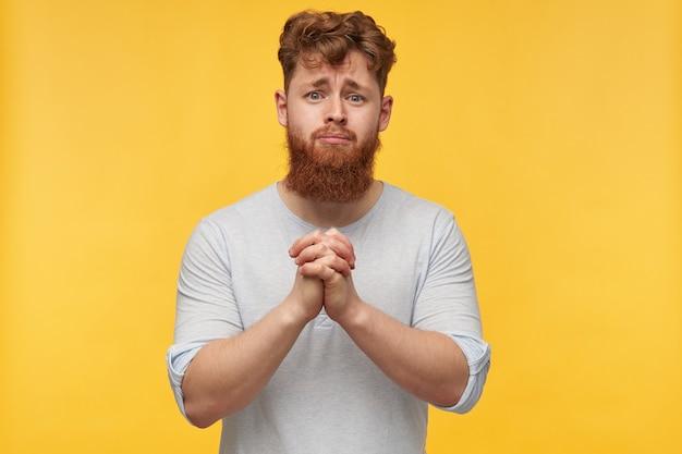 Ritratto di giovane maschio triste, con i capelli rossi e la grande barba, tiene insieme il palmo della mano nel gesto di preghiera, si sente abbracciato, per favore qualcuno in giallo.