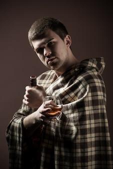 Ritratto di un giovane uomo triste che soffre di alcolismo avvolto in un plaid con un bicchiere e una bottiglia di alcolico nelle sue mani contro un muro scuro