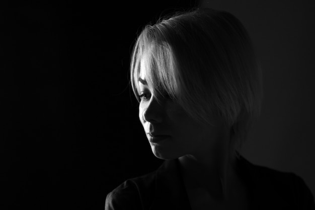 Ritratto di un primo piano di giovane donna triste che guarda lontano, foto in bianco e nero scuro