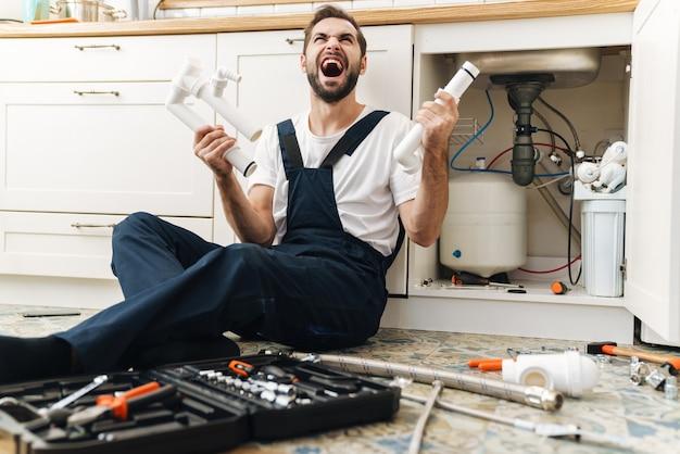 Il ritratto di giovane idraulico dell'uomo emotivo dispiaciuto urlante lavora in uniforme all'interno che tiene il tubo.