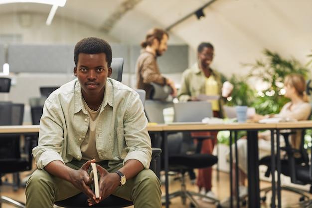 Ritratto di giovane serio afro-americano mentre è seduto in un ufficio moderno con persone che lavorano in superficie, copia dello spazio