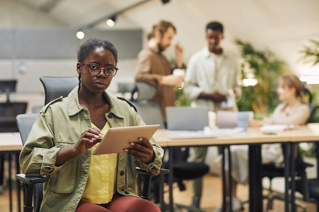 Ritratto di giovane donna afro-americana seria durante l'utilizzo di tavoletta digitale seduto in ufficio moderno con persone che lavorano in superficie, copia spazio