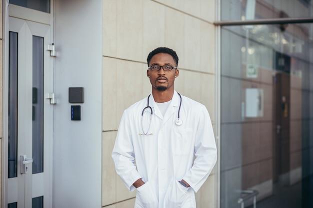 Ritratto di un giovane medico afroamericano serio, vicino alla clinica, in un abito medico bianco che guarda la telecamera