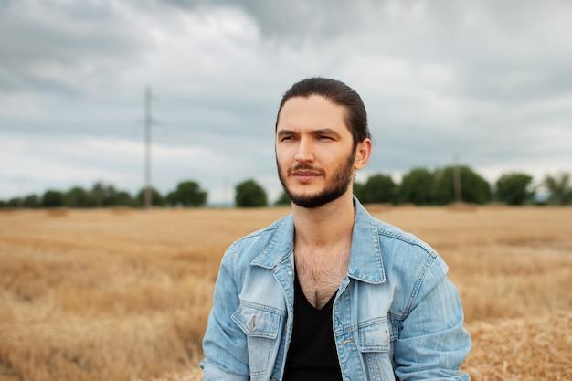 Ritratto di giovane uomo serio in giacca di jeans nel campo di grano.
