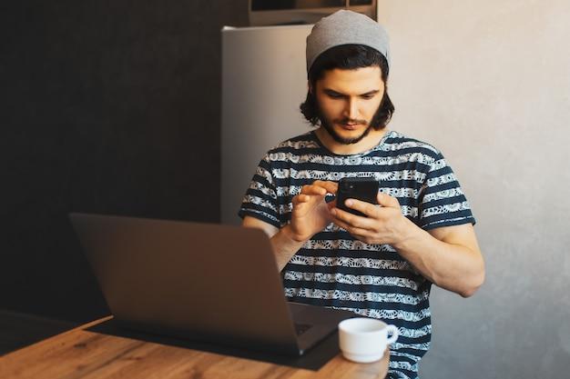 Ritratto di giovane uomo serio che digita sullo smartphone mentre si lavora al computer portatile e a volte beve caffè.
