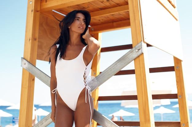 Ritratto di giovane ragazza sexy in costume da bagno bianco