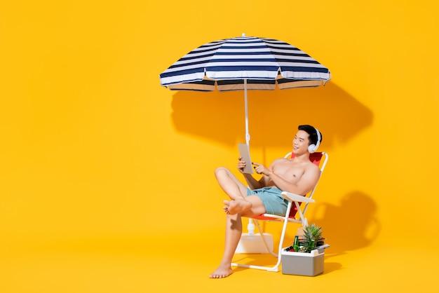 Ritratto di giovane uomo asiatico senza camicia che si siede sulla sedia di spiaggia che si rilassa e che ascolta la musica in parete isolata di giallo di estate
