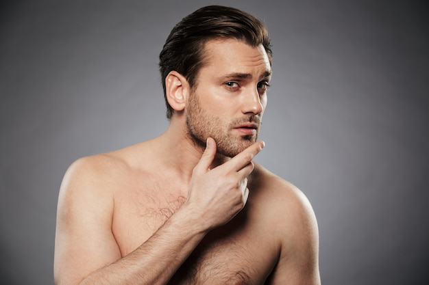 Ritratto di un giovane uomo senza camicia che esamina il suo viso