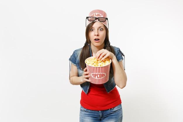 Ritratto di giovane donna attraente scioccata in occhiali 3d con secchio per popcorn sulla testa guardando film, mangiando popcorn dal secchio isolato su sfondo bianco. emozioni nel concetto di cinema.
