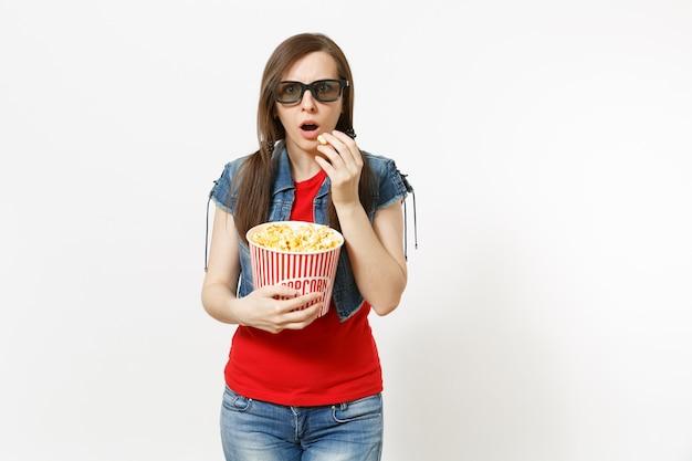 Ritratto di giovane bella donna castana scioccata in occhiali 3d, abbigliamento casual guardando film, tenendo e mangiando popcorn dal secchio isolato su sfondo bianco. emozioni nel concetto di cinema.
