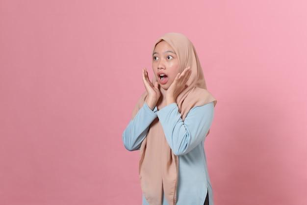 Ritratto di giovane donna musulmana scioccata che guarda lontano isolato su sfondo rosa