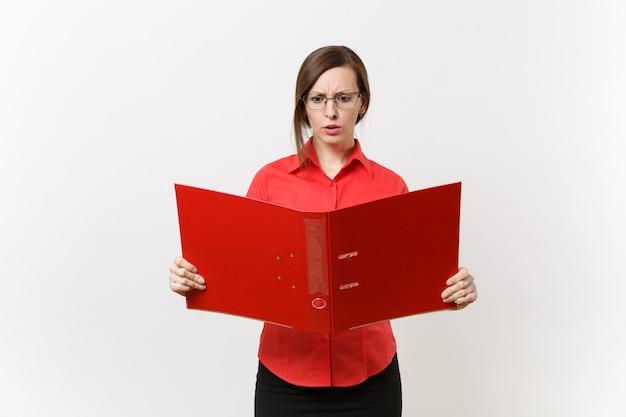 Ritratto di giovane donna scioccata triste insegnante di affari in camicia rossa, occhiali che tengono cartella con documenti di lavoro cartacei isolati su sfondo bianco. insegnamento dell'istruzione nel concetto di università delle scuole superiori.