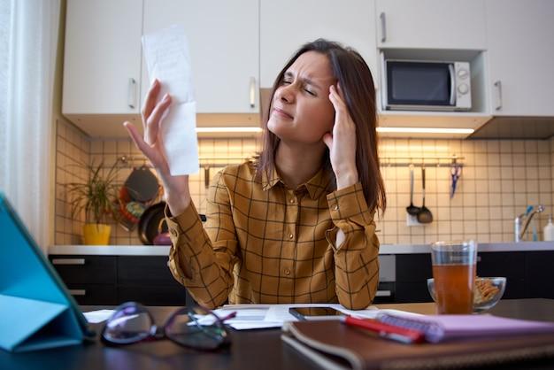 Ritratto di una giovane madre single bruna esplorando in conti bancari in cucina a casa