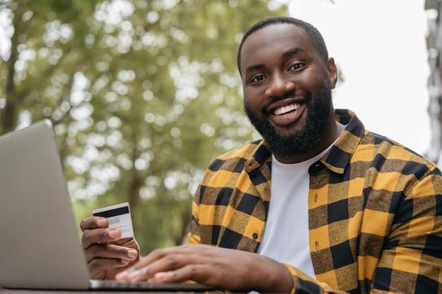 Ritratto di giovane afroamericano sorridente che tiene la carta di credito che compera in linea il concetto di black friday