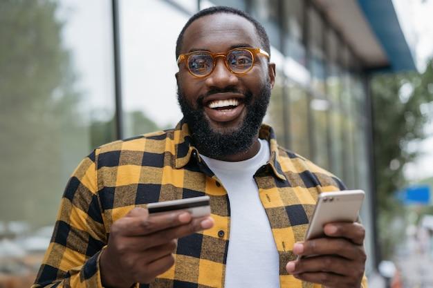 Ritratto di giovane uomo afroamericano sorridente che tiene la carta di credito, acquisti in linea