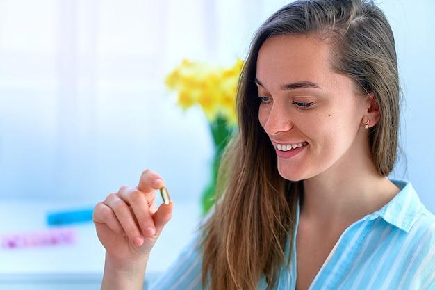 Ritratto di giovane donna felice attraente sorridente che prende integratore alimentare vitamina omega 3 per il supporto sanitario delle donne. softgel di olio di pesce, vitamina d e c per l'immunità e la prevenzione delle malattie