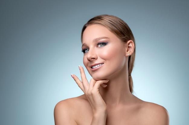 Ritratto di giovane bella donna bionda sorridente con trucco nudo.
