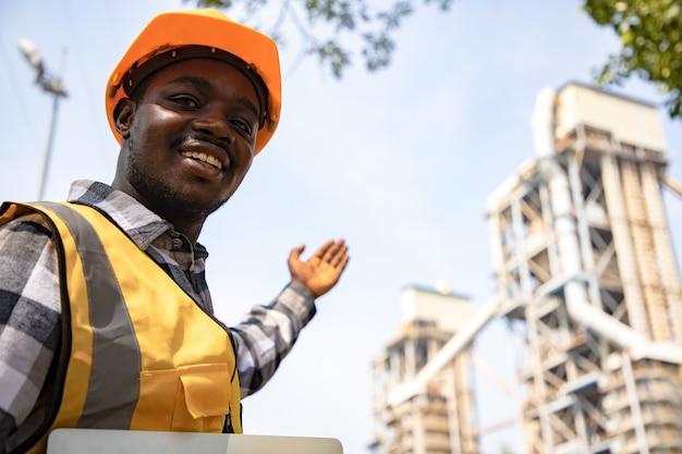 Ritratto di giovane lavoratore sorridente dell'ingegnere edile al sito
