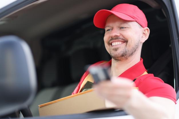 Ritratto di giovane corriere sorridente nel finestrino dell'auto con la scatola in mano