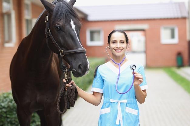 Ritratto di giovane veterinario femminile sorridente che tiene il campanile mentre si trova accanto al cavallo