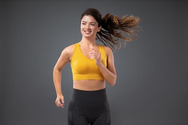 Ritratto di una giovane donna sorridente con una coda di cavallo in abiti sportivi che fa un leggero movimento del corpo isolato