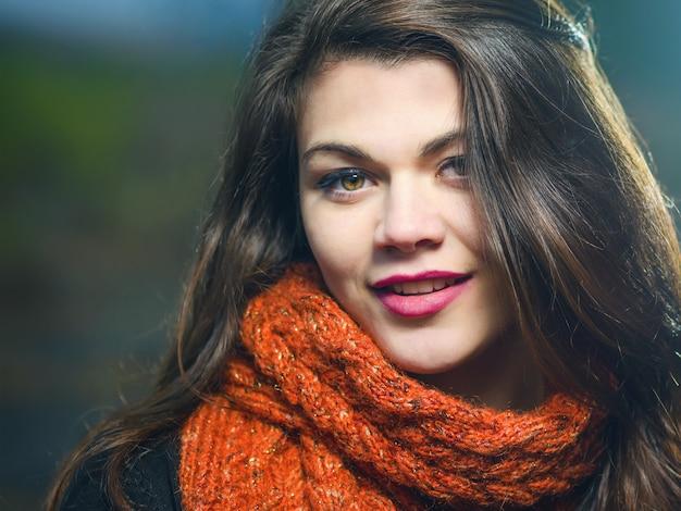 Ritratto di una giovane ragazza sorridente sera all'aperto. la luce blu illumina il modello. tonalità fredde