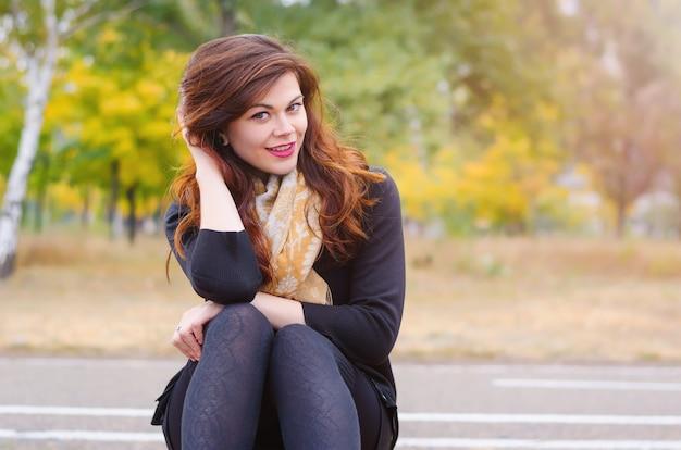 Ritratto di una giovane ragazza sorridente in una sciarpa, che si siede su una panchina nel parco in autunno. caldo clima autunnale e sole.