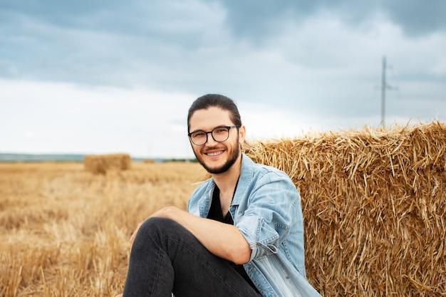 Ritratto di giovane ragazzo sorridente seduto nel campo di grano vicino a mucchi di fieno.