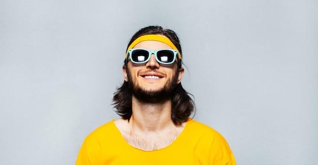 Ritratto di giovane ragazzo sorridente con i capelli lunghi che indossa occhiali da sole, camicia gialla e fascia sulla testa. fondo della parete strutturata grigia.