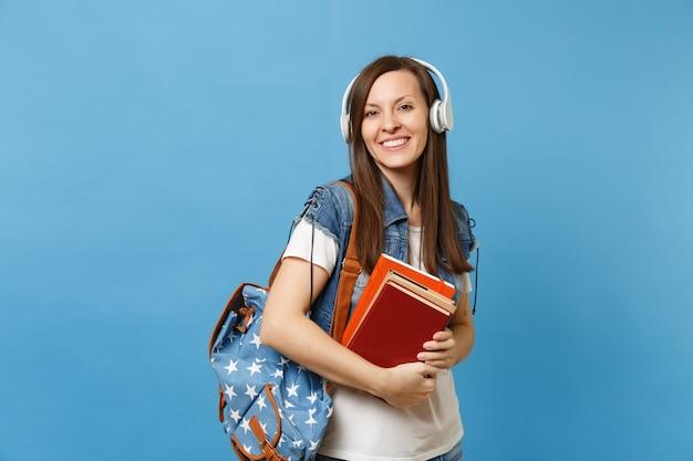 Ritratto di giovane studentessa adorabile sorridente in vestiti di denim con musica d'ascolto delle cuffie dello zaino, tenendo i libri di scuola isolati su fondo blu. istruzione al college universitario di scuola superiore.