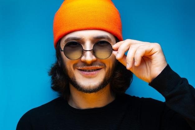 Ritratto di giovane uomo sorridente su sfondo blu. ragazzo con i capelli lunghi che indossa cappello arancione, occhiali da sole rotondi e maglione nero.