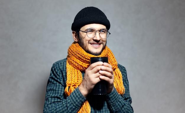 Ritratto di giovane uomo sorridente in camicia verde con sciarpa arancione e cappello a cuffia nero