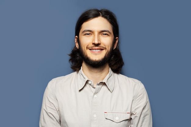 Ritratto di giovane uomo sorridente con i capelli lunghi su sfondo blu.