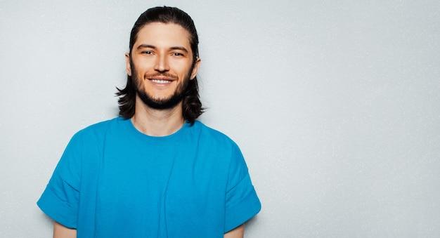 Ritratto di giovane uomo sorridente con capelli lunghi in camicia blu su fondo strutturato di grigio con lo spazio della copia.