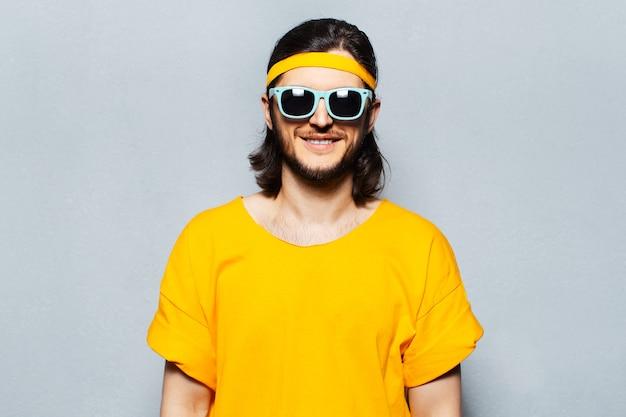 Ritratto di giovane uomo sorridente in occhiali da sole d'uso gialli su fondo strutturato di grigio.