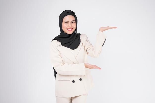Ritratto di giovane imprenditrice musulmana sorridente che indossa tuta con hijab su sfondo bianco studio.