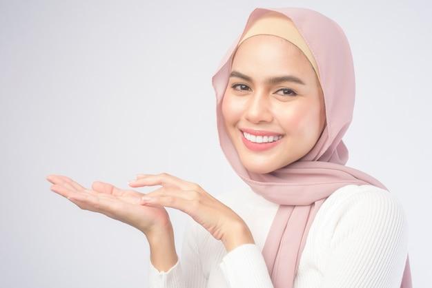 Un ritratto di giovane donna musulmana sorridente che indossa un hijab rosa su sfondo bianco studio.