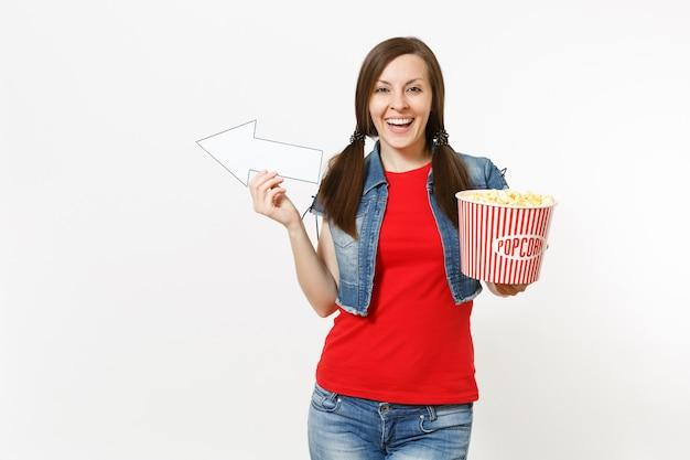 Ritratto di giovane donna sorridente in abiti casual che guarda film, tenendo secchio di popcorn, puntando la freccia bianca da parte su copyspace isolato su sfondo bianco. emozioni nel concetto di cinema.