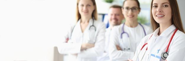 Ritratto di giovane dottoressa sorridente sullo sfondo dei colleghi
