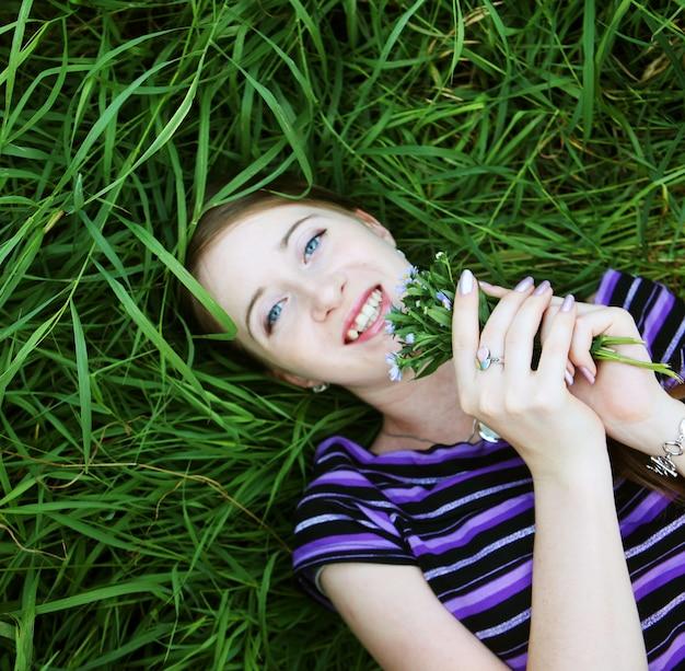 Ritratto di giovane donna sorridente sull'erba